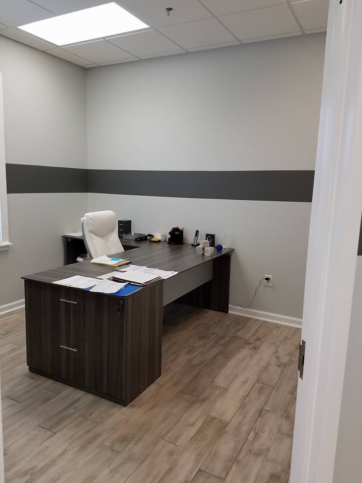 home office addition with desk and wood flooring