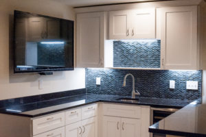 kitchen remodel with blue back splash and white cabinets